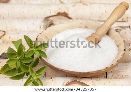 birch sugar and leaves of stevia on bitch background - stock photo
