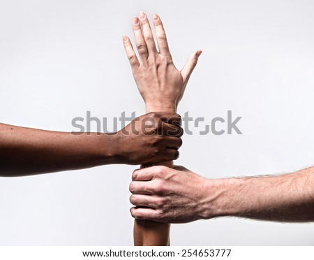 black African American and Caucasian hands holding together white skin arm in world unity and racial love , understanding in tolerance races diversity cooperation concept isolated on white background - stock photo