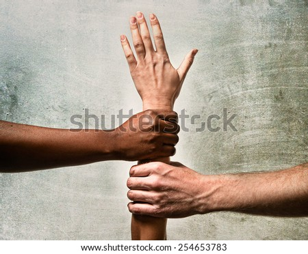 black African American and Caucasian hands holding together white skin arm in world unity and racial love and understanding in tolerance races diversity cooperation concept isolated studio background - stock photo
