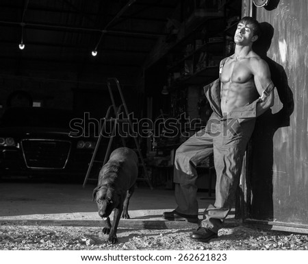 Black and white photo of young muscular guy with black dog near garage gate - stock photo