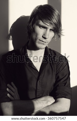 black and white portrait of a young sad man in black shirt - stock photo