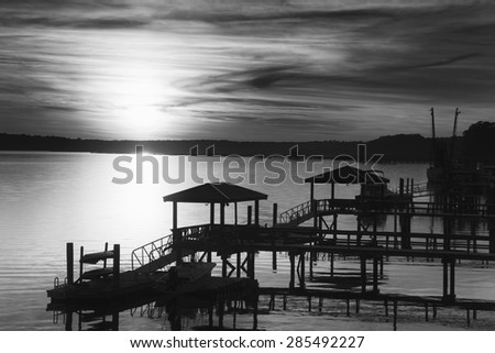 """""""Black and White View of the May River in SC"""" A few minutes before sunset on a beautiful March evening in Bluffton South Carolina, overlooking the docks on the May River at high tide. - stock photo"""
