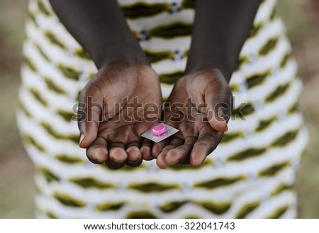 Black Girl Holding Pills Drugs to Cure Diseases in Africa. Unfortunately, in Africa there are lots of diseases like malaria, pneumonia, AIDS or simple Diarrhoea.  - stock photo