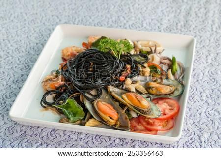 Black spaghetti in spicy sea food - stock photo