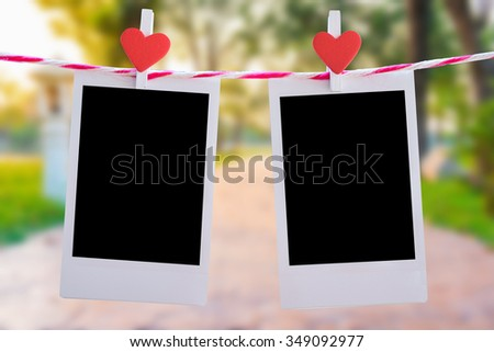 2 Blank instant photo and red clip paper heart hanging on the clothesline with nature bokeh background..Designer concept. - stock photo