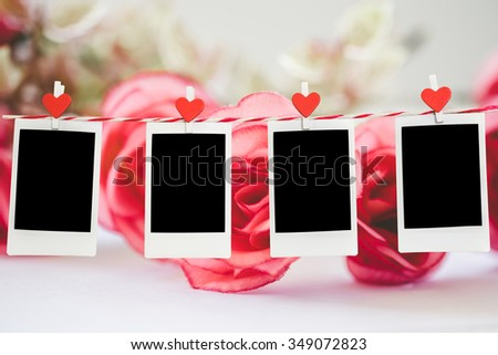4 Blank instant photo and red clippaper heart hanging on the clothesline with pink rose flower background. vintage tone.Designer concept. - stock photo