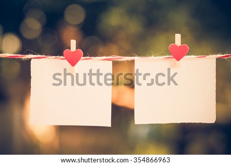 2 Blank white paper and red clip paper heart hanging on the clothesline with bokeh nature background.Designer concept.vintage or retro tone. - stock photo