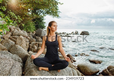 blond young women doing yoga with the ocean behind - stock photo
