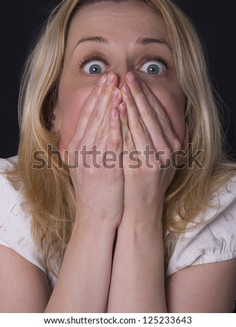 blonde woman covering her mouth with her hands - stock photo