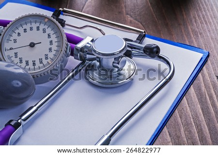 blood pressure monitor and stethoscope on clipboard with blank sheet medical concept - stock photo