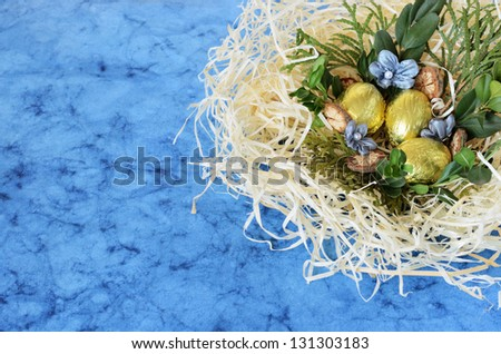 Blue background with arrangement with golden eggs and nest in the corner - stock photo