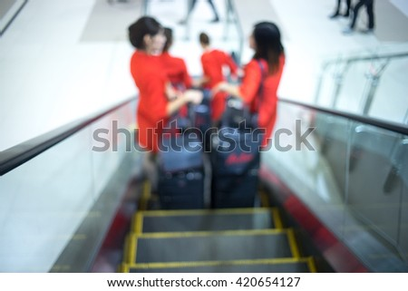 Blurred image of cabin crew walking at the airport terminal,cabin crew carrying their luggage. motion blurred - stock photo