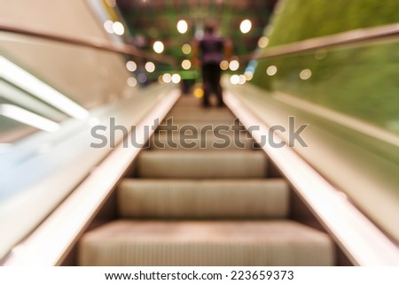 Blurred moving escalator shot by slow shutter speed - stock photo