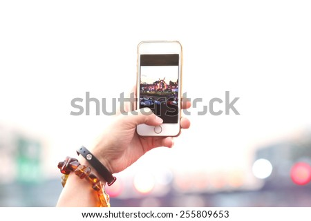 blurred people take photo , hand hold phone take photo in concert and travel up to sky with purple light background, internet and communication lifestyle. - stock photo