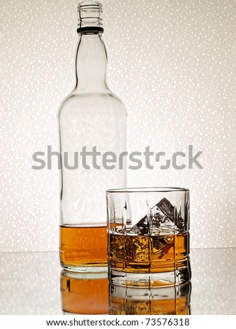 Bottle and glass of whiskey against white background. - stock photo