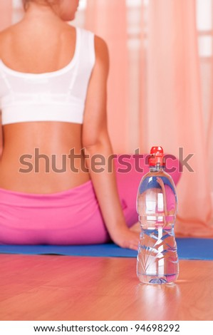 Bottle of water in front of sporty woman - stock photo