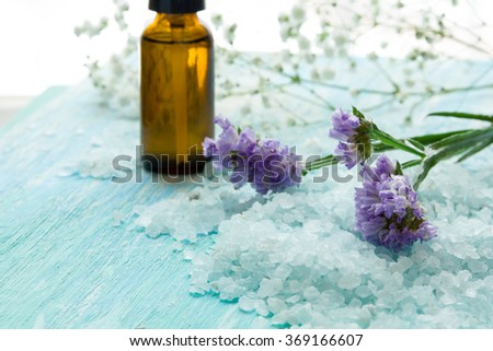 bottles essential oil and sea salt on a blue wooden table, Spa with flowers - stock photo