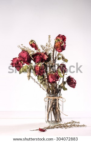 Bouquet of red dried roses in glass vase on white background - stock photo
