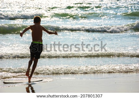 Boy moves on the surf board (alongside the sea shore) at sunset. Back view. (Brittany, France). Freedom concept. - stock photo