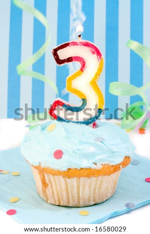 boy's third birthday cupcake with blue frosting and  decorative background - stock photo