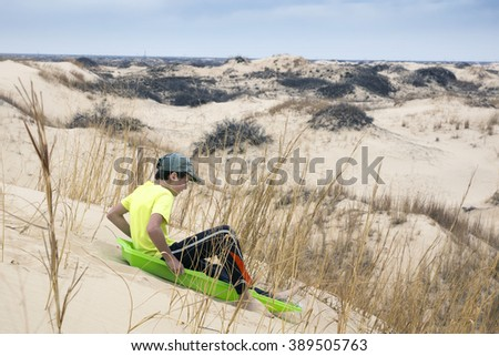 Boy sledding with sand dunes. Monahans Sandhills State Park, Texas, USA - stock photo