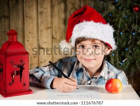 Boy writes a letter to Santa - stock photo