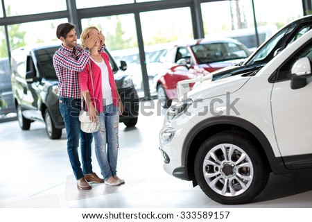 Boyfriend covering the eyes of his girlfriend for a surprise in car showroom - stock photo