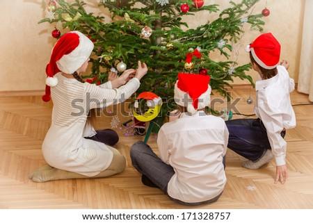 boys and girl decorate christmas tree - stock photo