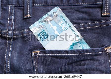 100 Brazilian Reais on the jeans pocket - stock photo