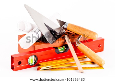 brick, mason tools and construction plans - stock photo