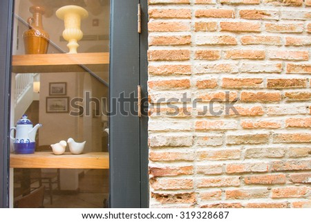 Brick wall, birds doll sit on the shelf that can see through Glass window - stock photo