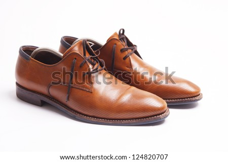 Brown leather men's shoes with wooden shoe stretchers on the side - stock photo