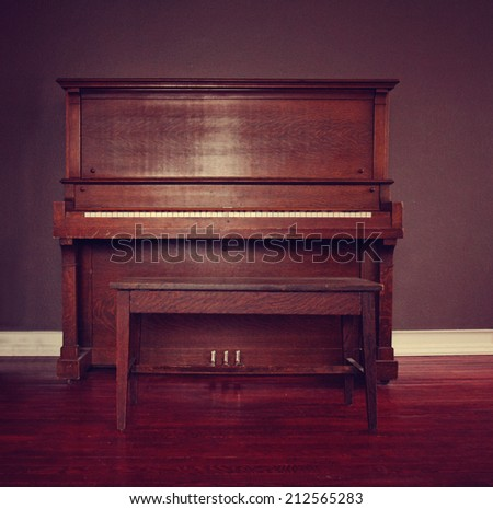 brown upright piano in a living room toned with a retro vintage instagram filter effect  - stock photo