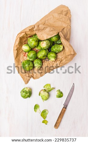 Brussels sprouts in paper bags on white wooden table - stock photo