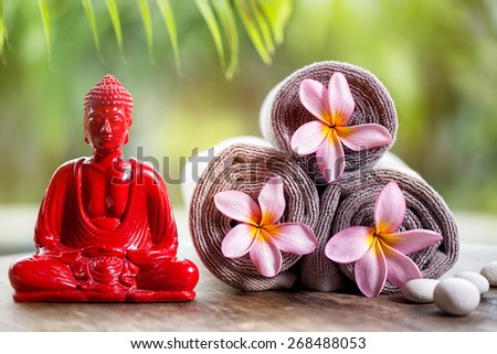 Buddha and flower in towels, wellness background - stock photo
