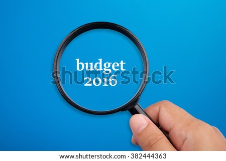 Budget 2016. Hand holding magnifying glass focusing on the words. - stock photo