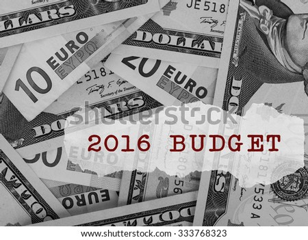 2016 budget text on a paper scrap over dollar and euro banknotes - stock photo