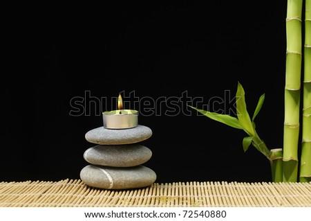 Burning candle on stones with bamboo grove on black background - stock photo