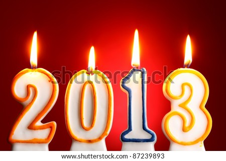 2013 burning candles close-up over red background - stock photo