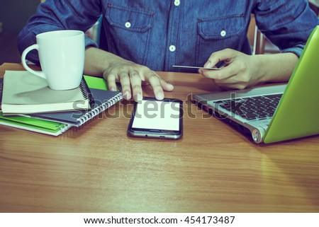 Business Man holding a credit Working With Modern Devices, Digital Computer And Mobile Phone(Vintage) - stock photo
