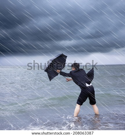 business man holding a umbrella to resist rainstorm  - stock photo