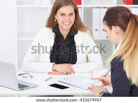 Business, office, law and legal concept - picture of two woman signing contract paper. - stock photo