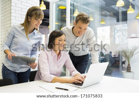Business team working on laptop in modern office - stock photo