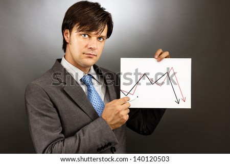 Businessman drawing a falling graph of stock market against gray - stock photo