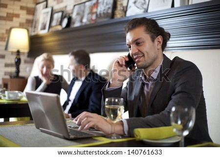 Businessman using laptop in cafe - stock photo