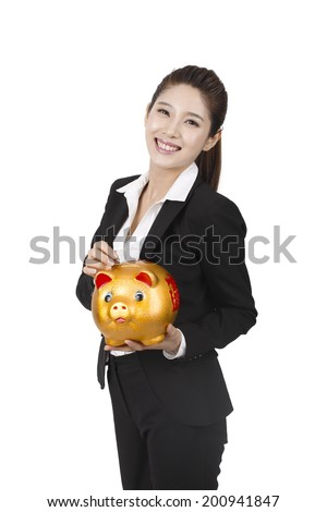 Businesswoman putting coin into piggy bank - stock photo
