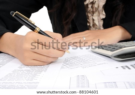 businesswoman's hand writing with pen and calculator, isolated on white background - stock photo