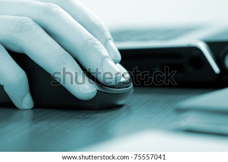 Businesswoman working with her laptop - blue toned image - stock photo