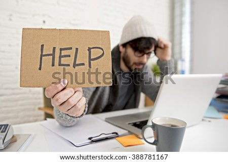 busy hispanic hipster 30s businessman working tired at home office with computer laptop dressing casual asking for help looking overworked  suffering stress and depression - stock photo