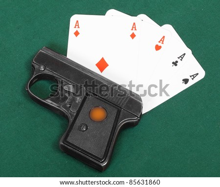 .22 cal semiautomatic pistol and four aces. Hazard metaphor. - stock photo